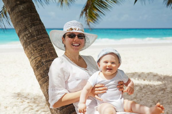 Holiday Baby and Children. Lady with Baby on beach under a Palm Tree.