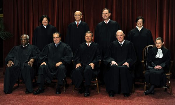 U.S. Supreme Court Justices Clarence Thomas, front row from left to right, Antonin Scalia, John G. Roberts, Anthony Kennedy, Ruth Bader Ginsburg, Sonia Sotomayor, back row from left to right, Stephen Breyer, Sameul Alito, and Elena Kagan sit for a group photograph in the East Conference Room of the Supreme Court in Washington, D.C., U.S., on Friday, Oct. 8, 2010. With the appointment of Kagan, the nine-member supreme court now has three women for the first time. Photographer: Roger L. Wollenberg/Pool via Bloomberg