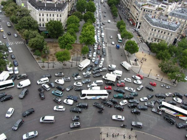 Image of over 100 cars, buses and trucks trying to circumnavigate a busy Paris roundabout. Used to illustrate the challenges when driving abroad.
